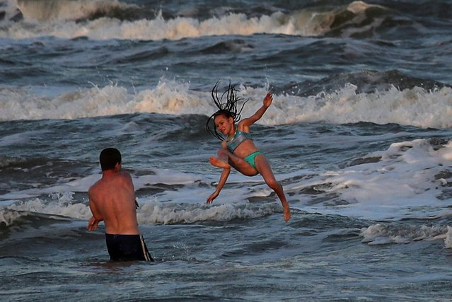 Troy Aller throws his cousin Taliyah, 10, into the surf at a closed beach during the coronavirus disease (COVID -19) pandemic in Surfside Beach, Texas, U.S., April 27, 2020. (Photo by Adrees Latif/Reuters)
