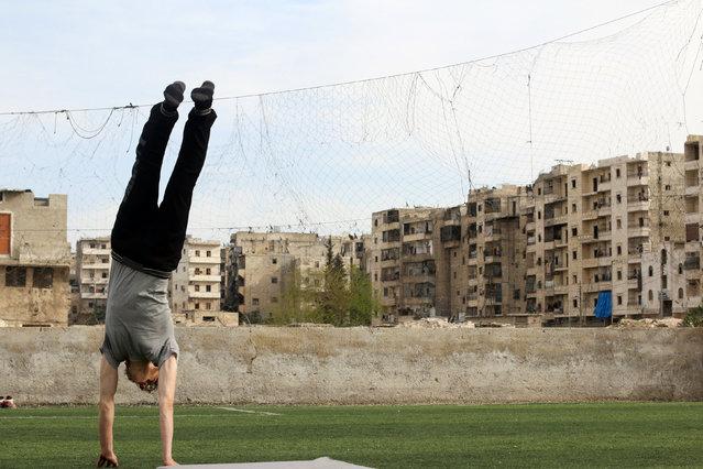 Gymnast Ahmad al-Sawas practises in the rebel-held Bustan al-Qasr neighbourhood of Aleppo, Syria March 23, 2016. (Photo by Abdalrhman Ismail/Reuters)