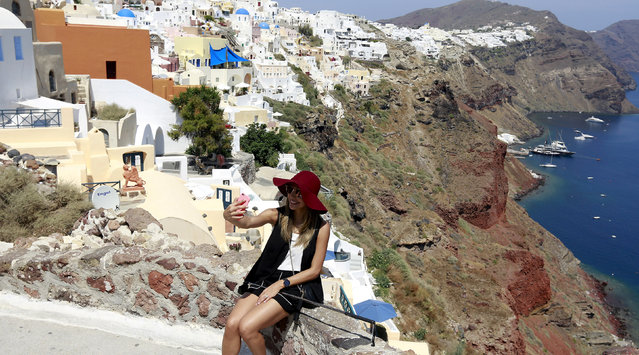 A tourist takes a selfie in the village of Oia on the Greek island of Santorini, Greece, July 1, 2015. (Photo by Cathal McNaughton/Reuters)