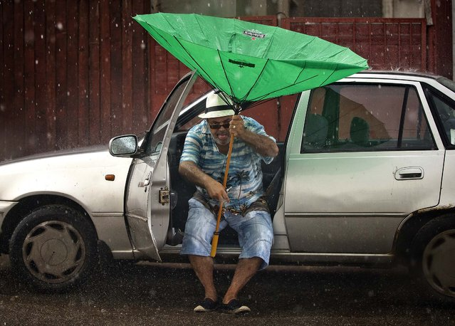 A man uses a damaged umbrella while boarding a car during a thunderstorm in Bucharest, Romania, on August 8, 2014. (Photo by Vadim Ghirda/Associated Press)