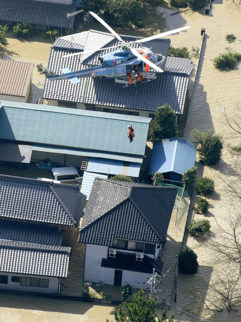 A stranded resident is airlifted by a helicopter during a rescue operation in Joso, Ibaraki prefecture, northeast of Tokyo, Friday, September 11, 2015. (Photo by Masanori Takei/Kyodo News via AP Photo)