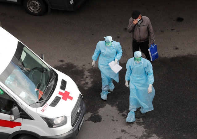 A man wearing a protective mask walks behind medical specialists outside Pokrovskaya hospital, which delivers medical aid to patients infected with the coronavirus disease (COVID-19) in Saint Petersburg, Russia on April 27, 2020. (Photo by Anton Vaganov/Reuters)