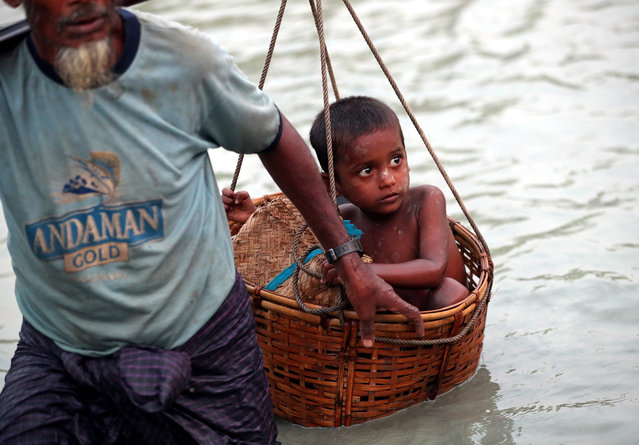 A Rohingya refugee boy is carried across the Naf River as they cross the Myanmar-Bangladesh border in Palong Khali, near Cox's Bazar, Bangladesh on November 1, 2017. (Photo by Hannah McKay/Reuters)