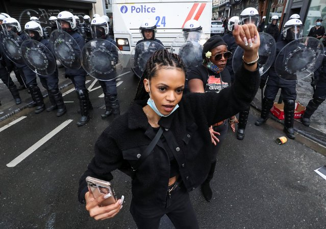 A demonstrator holds up her fist, in front of police officers during a protest, organised by Black Lives Matter Belgium, against racial inequality in the aftermath of the death in Minneapolis police custody of George Floyd, in central Brussels, Belgium on June 7, 2020. (Photo by Yves Herman/Reuters)