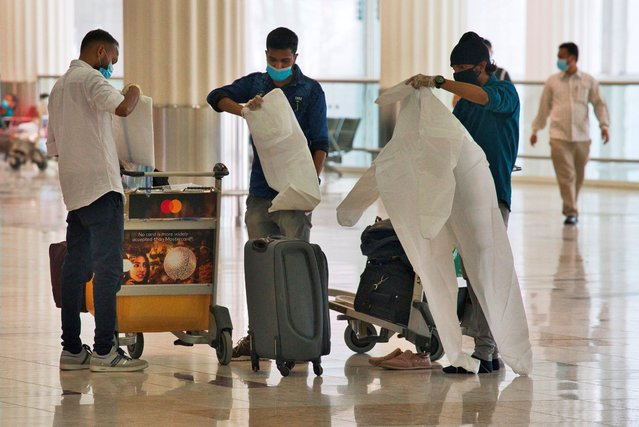 Passengers wearing masks due to the coronavirus pandemic put on throwaway coveralls before their flight at Dubai International Airport's Terminal 3 in Dubai, United Arab Emirates, Wednesday, June 10, 2020. The coronavirus pandemic has hit global aviation hard, particularly at Dubai International Airport, the world's busiest for international travel, due to restrictions on global movement over the virus. (Photo by Jon Gambrell/AP Photo)