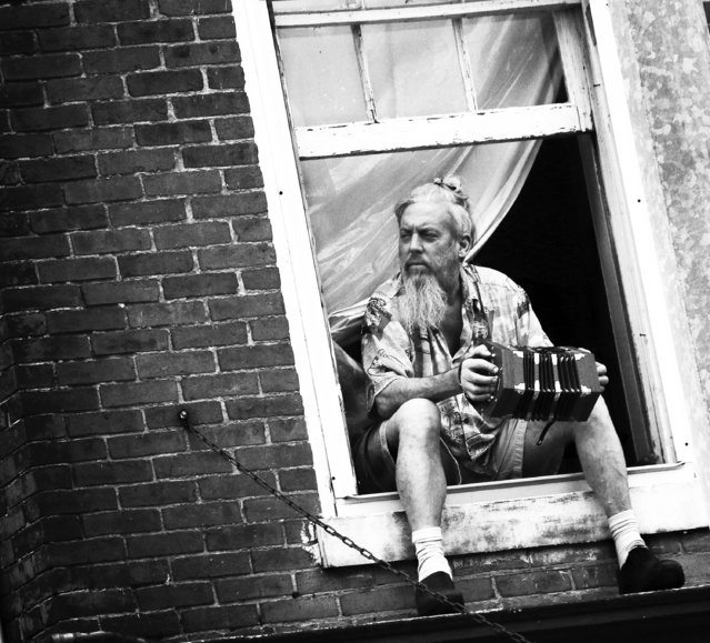 """""""Playful Observer"""". A man sits in the window of his second-story apartment playing music while waiting for the parade to start. The parade was part of the Iron Horse Festival, which serves as a homecoming and celebration of heritage in New Haven, Kentucky. Photo location: New Haven, Kentucky, United States. (Photo and caption by Kacie Goode/National Geographic Photo Contest)"""