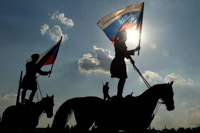 Riders hold the Russian national flag in Moscow on August 22, 2016, during celebrations of the National Flag Day. Russia marks the 25th anniversary of the abortive 1991 coup against then Soviet president Mikhail Gorbachev. August 22, 1991, when Russia's flag was raised atop the Russian White House instead of the Soviet one was declared as Russia's Flag Day. (Photo by Vasily Maximov/AFP Photo)