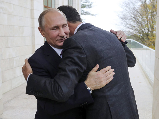 In this Monday, November 20, 2017, photo, Russian President Vladimir Putin, left, embraces Syrian President Bashar Assad in the Bocharov Ruchei residence in the Black Sea resort of Sochi, Russia. Putin has met with Assad ahead of a summit between Russia, Turkey and Iran and a new round of Syria peace talks in Geneva, Russian and Syrian state media reported Tuesday. (Photo by Mikhail Klimentyev/Kremlin Pool Photo via AP Photo)