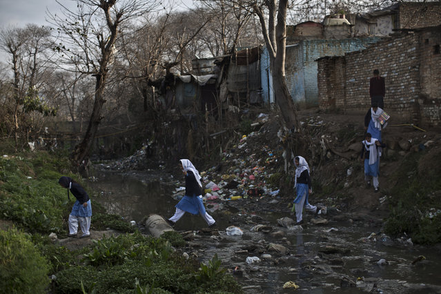 In this Tuesday, March 4, 2014, photo, Pakistani schoolgirls cross a stream of sewage and rubbish that separates their neighborhood from the main road, heading to their school in Islamabad, Pakistan. Malala's struggle for girls to be educated in a deeply conservative society led to her shooting by the Taliban two years ago, while her relentless campaign for women's was rewarded Friday, October 10, by the recognition of her work as she was jointly awarded the Nobel Peace Prize. (Photo by Muhammed Muheisen/AP Photo)