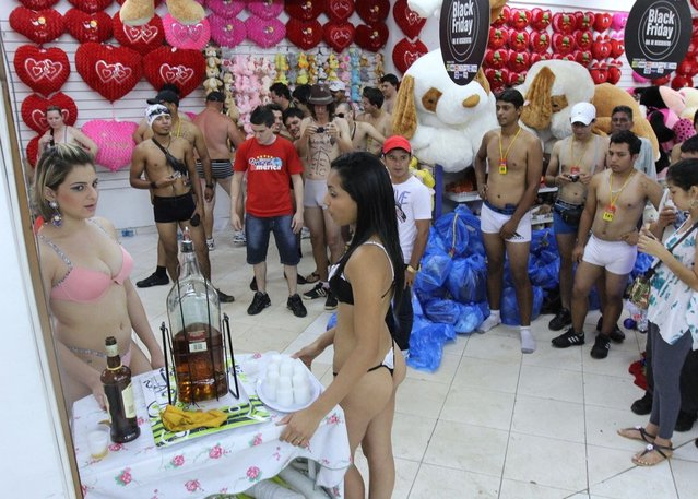 Customers (R) and hostess (L) in underwear take part in a special promotion at a mall in Ciudad del Este, Paraguay, on December 2, 2012.   AFP PHOTO/ JOSE ESPINOLA        (Photo credit should read JOSE ESPINOLA/AFP/Getty Images)
