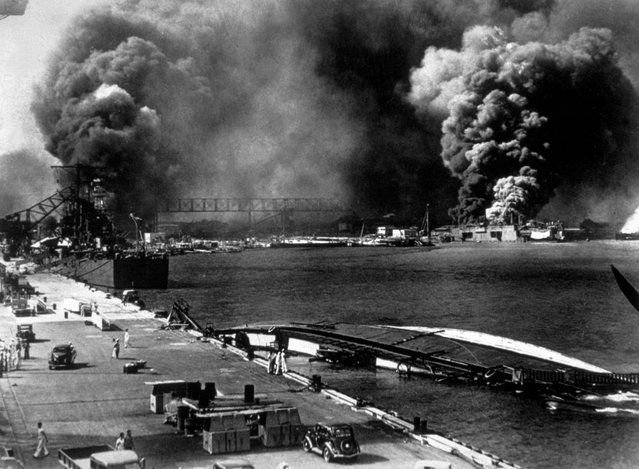 7th December 1941:  A general view of Pearl Harbour (Pearl Harbor) after it had been attacked by the Japanese. Smoke pours from USS Shaw (right centre) whilst the minelayer USS Oglana lies capsized in the foreground.  (Photo by Keystone/Getty Images)
