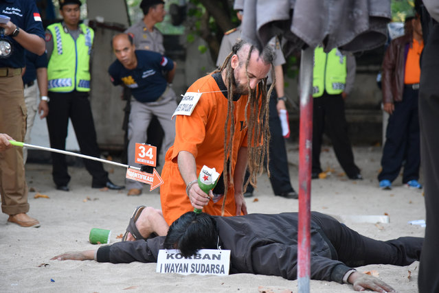 British man David Taylor re-enacts a scene as a police officer poses as victim Wayan Sudarsa on Kuta Beach in Bali, Indonesia, August 31, 2016. (Photo by Lauren Farrow/Reuters/AAP)