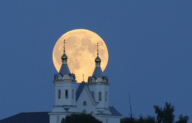 A perigee moon, also known as a super moon, rises above the Orthodox Church in the town of Novogrudok, 150 kilometers (93 miles) west of the capital Minsk, Belarus, Saturday, August 29, 2015. The supermoon happens when moon is full and makes it closest approach to Earth in her orbit. (Photo by Sergei Grits/AP Photo)