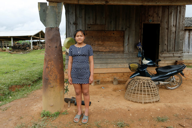 A girl poses at an entrance of her house next to a bomb dropped by the U.S. Air Force planes during the Vietnam War, in the village of Ban Napia in Xieng Khouang province, Laos September 3, 2016. (Photo by Jorge Silva/Reuters)