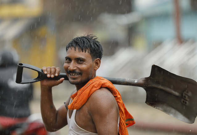 An Indian worker crosses a street holding a shovel during monsoon rains in Prayagraj, in the northern Indian state of Uttar Pradesh, Wednesday, July 29, 2020. (Photo by Rajesh Kumar Singh/AP Photo)
