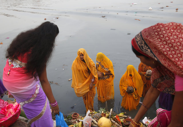 Hindu Women worship the Sun god Surya in the waters of the river Yamuna during the Hindu religious festival of Chatt Puja in New Delhi October 29, 2014. (Photo by Ahmad Masood/Reuters)