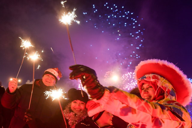 People light sparklers during New Year celebrations in central Novosibirsk, Russia on December 31, 2017. (Photo by Kirill Kukhmar/TASS via Getty Images)