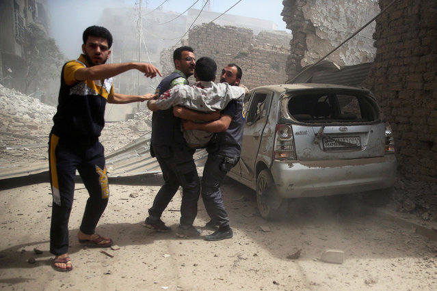 Civil defense members assist an injured man after an airstrike in the rebel held Douma neighborhood of Damascus, Syria September 9, 2016. (Photo by Bassam Khabieh/Reuters)