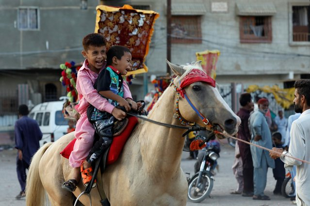 Children ride on a horse at a playground in a slum as public places remain closed as preventive measures against the coronavirus during Eid al-Adha celebration, in Karachi, Pakistan on August 2, 2020. (Photo by Akhtar Soomro/Reuters)