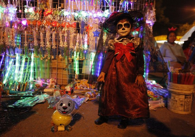 """Kimberli, 4, dressed up with her face painted as the popular Mexican figure """"Catrina"""", poses for a photograph with her plastic dog in front of a street vendor's stall in Ciudad Juarez late November 2, 2014. The character """"Catrina"""", also known as the """"The Elegant Death"""", was created by Guadalupe Posada in the early 1900s and has become an important part of Mexico's celebrations of the Day of the Dead on November 1 and 2. (Photo by Jose Luis Gonzalez/Reuters)"""