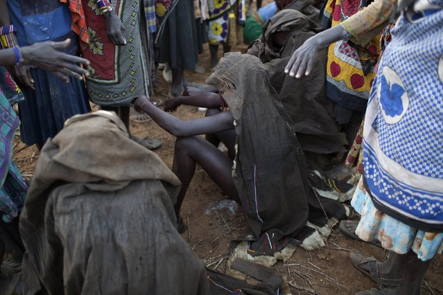 Pokot girls, draped in animal skins, sit on rocks during their circumcision ceremony in a village about 80 kilometres from the town of Marigat in Baringo County, October 16, 2014. (Photo by Siegfried Modola/Reuters)