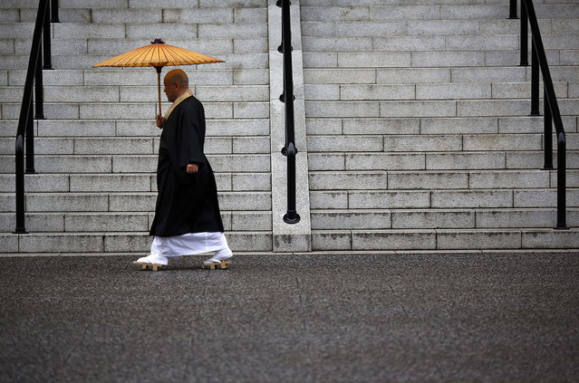 A Buddhist monk walks in the rain at Sensoji Buddhist temple at Asakusa district in Tokyo, Saturday, November 8, 2014. Asakusa is an old town in the capital that draws many tourists from across the world. (Photo by Eugene Hoshiko/AP Photo)
