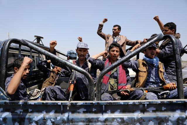 Houthi-affiliated security troopers shout slogans as they ride on the back of a patrol truck at the site of a protest against a decision by the United Arab Emirates to normalize ties with Israel, in Sanaa, Yemen on August 22, 2020. (Photo by Khaled Abdullah/Reuters)