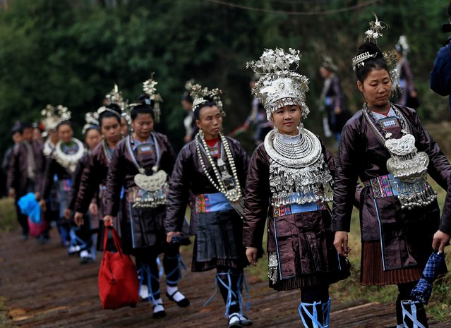 Ethnic Dong women wearing traditional costumes make their way to sing at an inauguration ceremony of a Dong culture Museum in Tongguan village, Liping county, Guizhou province, November 22, 2014. As part of a Tongguan tradition, people hold a feast and sing folk songs for wedding and inauguration ceremonies in the village. (Photo by Sheng Li/Reuters)
