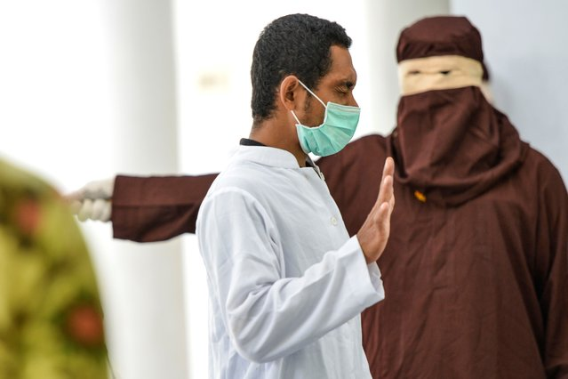 A man, convicted of engaging in sеxual activity with a minor, is flogged by a member of the Sharia police in a public building in Banda Aceh on September 24, 2020. Aceh is the only region in the world's biggest Muslim-majority nation that imposes Islamic law – known as Sharia – with those found guilty of breaches often publicly whipped with a rattan cane. (Photo by Chaideer Mahyuddin/AFP Photo)