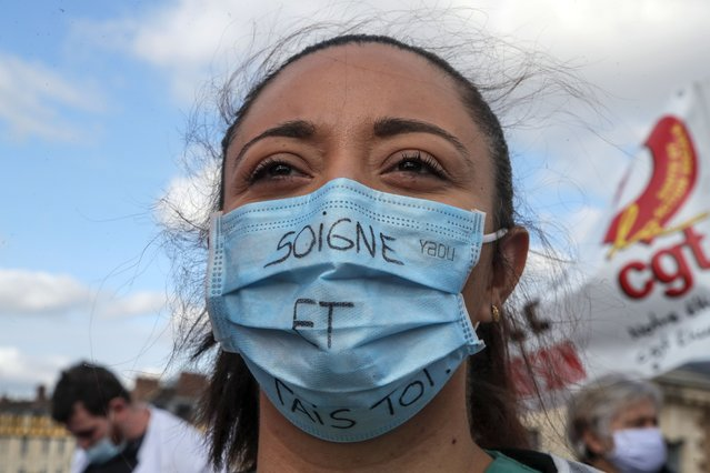 "A medical worker wears as mask that reads ""heal and shut up"", as she demonstrates to demand better salaries and working conditions in Paris, Thursday, October 15, 2020. French President Emmanuel Macron has announced that millions of French citizens in several regions around the country, including in Paris, will have to respect a 9pm curfew from this Saturday until Dec. 1. It's a new measure aimed at curbing the resurgent coronavirus amid second wave. The measures will require citizens in certain regions where the coronavirus is circulating to be at home after 9pm. (Photo by Michel Euler/AP Photo)"