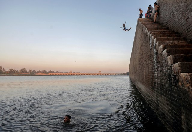 A boy jumps in the Nile River during hot weather on the outskirts of Cairo, following the outbreak of the coronavirus disease (COVID-19), Egypt on August 18, 2020. (Photo by Mohamed Abd El Ghany/Reuters)