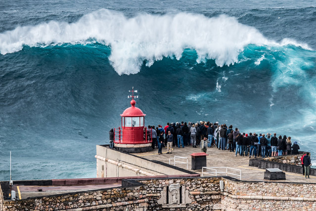 Crowds watch surfers as the first big swell of the year arrives in Nazaré, Portugal on October 28, 2015. (Photo by Pedro Miranda/Demotix/Corbis)