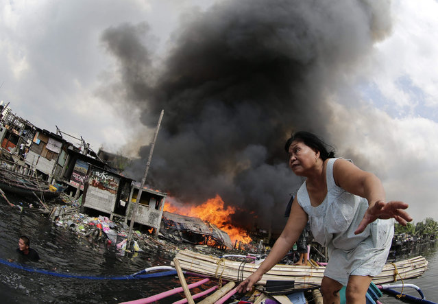 An elderly Filipino woman escapes from a fire in Paranaque city, south of Manila, Philippines, 29 October 2015. The Bureau of Fire Protection Chief Director Ariel Barayuga reminded the public to be extra cautious when lighting candles during the observance of All Soul's and All Saints' Day this week. Millions of Filipinos will soon flock to cemeteries around the country to visit departed relatives and loved ones to mark All Saints Day and All Souls Day on 01 and 02 November. (Photo by Francis R. Malasig/EPA)