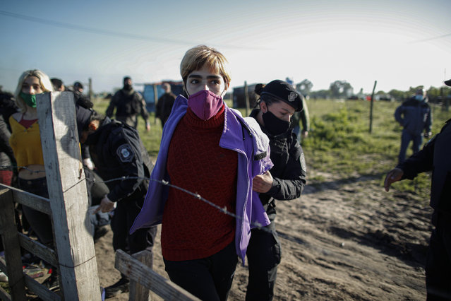 Women are detained by police carrying out evictions at a squatters camp in Guernica, Buenos Aires province, Argentina, Thursday, October 29, 2020. A court ordered the eviction of families who are squatting here since July, but the families say they have nowhere to go amid the COVID-19 pandemic. (Photo by Natacha Pisarenko/AP Photo)