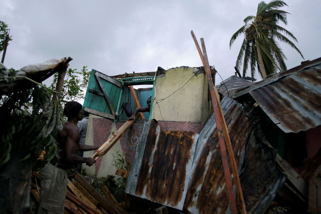 Men work amongst the wreckage of a house destroyed by Hurricane Matthew in Les Cayes, Haiti, October 5, 2016. (Photo by Andres Martinez Casares/Reuters)