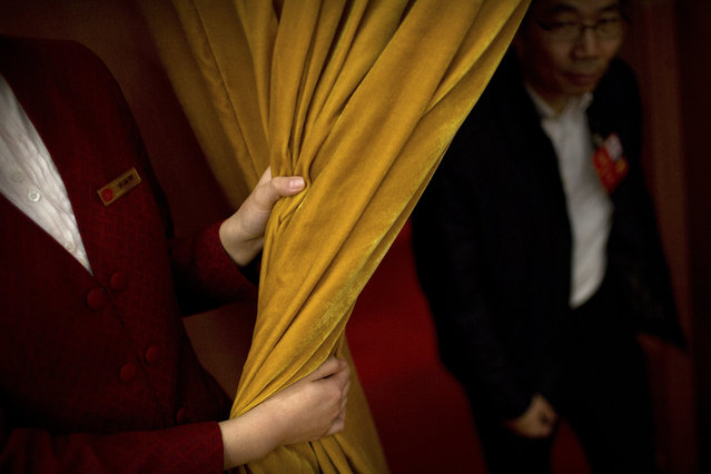 In this Friday, March 9, 2018 photo, an attendant pulls back a curtain for a delegate during a plenary session of China's National People's Congress (NPC) at the Great Hall of the People in Beijing. The annual conclave of China's National People's Congress is a carefully scripted affair, but the actual decision-making happens out of sight and away from prying eyes. (Photo by Mark Schiefelbein/AP Photo)