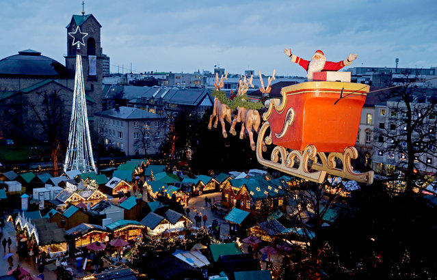 """High wire performer Falko Traber poses as the """"Flying Santa"""" on his motorcycle shaped like a reindeer sleigh above the Christmas Market in Karlsruhe, Germany, Thursday, Dec. 11, 2014. (Photo by Ronald Wittek/AP Photo/DPA)"""