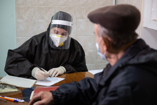 A medical worker registers a man at the Lugansk City Hospital No 1 which treats COVID-19 patients in Lugansk, Ukraine on October 29, 2020. (Photo by Alexander Russky/TASS)