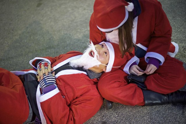 "A couple in Santa Claus outfits attend an after-party for the ""Running of the Santas"" at the Electric Factory in Philadelphia, Pennsylvania December 13, 2014. (Photo by Mark Makela/Reuters)"