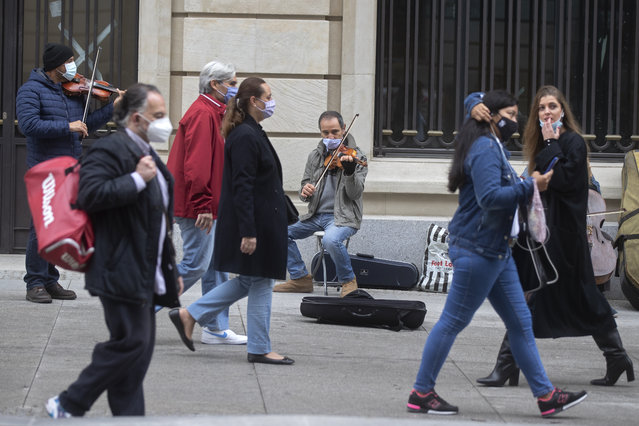 Street musicians play for passers-by in Madrid, Spain, Sunday, November 15, 2020. Spain continues with new measures against the COVID-19 while suffering a second strong pandemic crisis by Coronavirus. (Photo by Paul White/AP Photo)