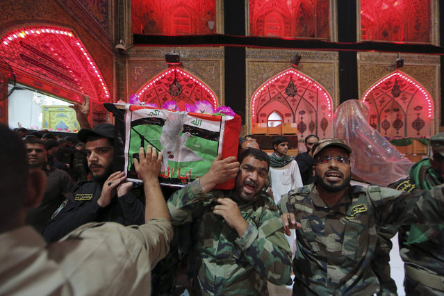 Mourners and militiamen chant slogans against the Islamic State group as they carry one of two flag-draped coffins of members of the Peace Brigades, a Shiite militia group loyal to Shiite cleric Muqtada al-Sadr, during their funeral procession inside the shrine of Imam Ali in Najaf, 100 miles (160 kilometers) south of Baghdad, Iraq, Saturday, November 7, 2015. The militiamen were killed in Ramadi during fighting with Islamic State militants, their families said. (Photo by Anmar Khalil/AP Photo)