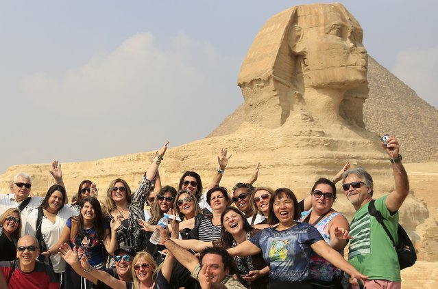 Tourists smile and cheer as they take a souvenir photo in front of the Sphinx at the Giza Pyramids on the outskirts of Cairo, Egypt, November 8, 2015. (Photo by Amr Abdallah Dalsh/Reuters)