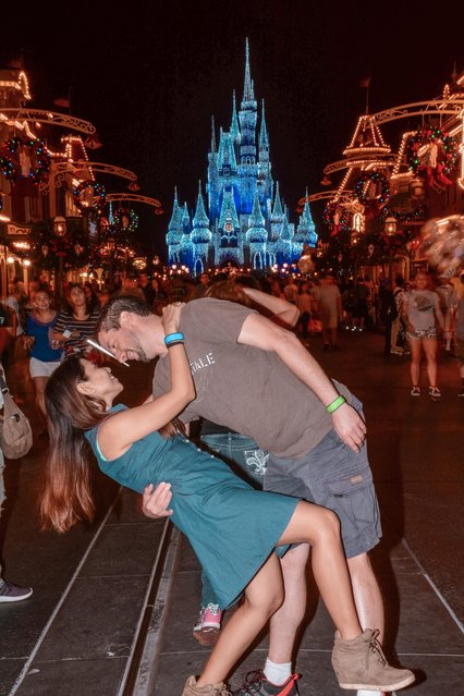 Husband and wife Rob 34 and Joli Switzer 33 from Maryland,  their DipKiss pose at DisneyWorld Florida in front of the Magic Kingdom. (Photo by Dipkiss Travels/Caters News Agency)