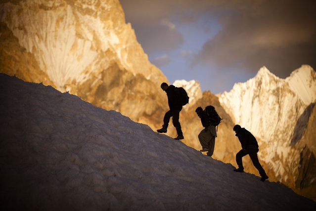 Expedition members meander between crevasses with the Gasherbrum IV massif visible in the background. (Photo by David Kaszlikowski/Rex Features)