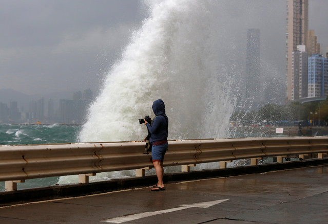 A man takes a photo on a waterfront as Typhoon Haima approaches in Hong Kong, China, October 21, 2016. (Photo by Bobby Yip/Reuters)