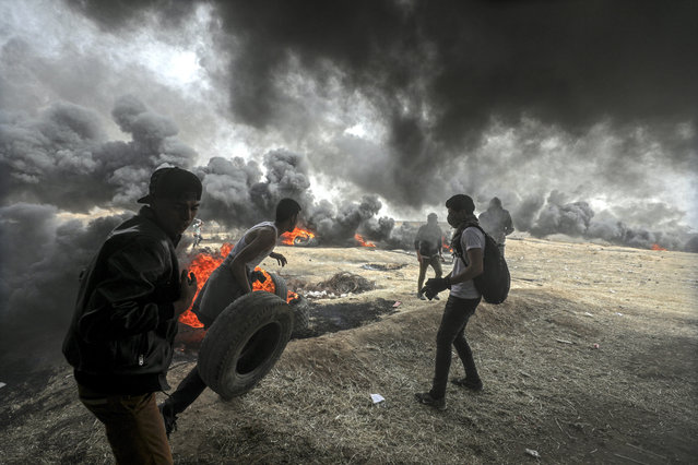 Palestinians protesters during clashes near the border with Israel in the east of Gaza City, 20 April 2018. According to reports, Two Palestinians youths protesters were killed by Israeli bullets and more than 120 others wounded during the clashes near the border between Israel and Gaza Strip. Protesters plan to call for the right of Palestinian refugees across the Middle East to return to homes they fled in the war surrounding the 1948 creation of Israel. (Photo by Mohammed Saber/EPA/EFE)