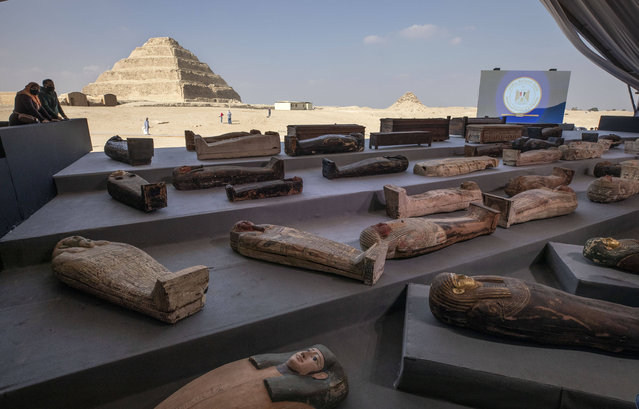 People look at ancient sarcophagi on display, discovered in a vast necropolis in Saqqara, Giza, Egypt, Saturday, November 14, 2020. Egyptian antiquities officials on Saturday announced the discovery of at least 100 ancient coffins, some with mummies inside, and around 40 gilded statues south of Cairo. (Photo by Nariman El-Mofty/AP Photo)