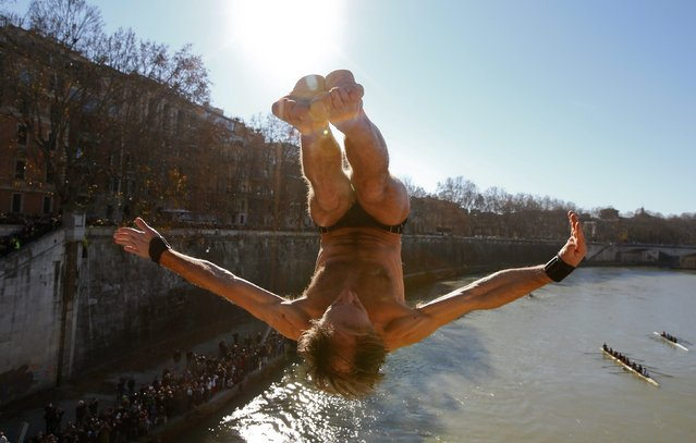 Marco Fois of Italy dives into the Tiber River from the Cavour bridge, as part of traditional New Year celebrations in Rome January 1, 2015. (Photo by Tony Gentile/Reuters)