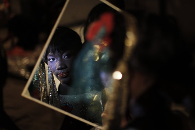 A Senegalese model is reflected in a mirror backstage during Dakar Fashion Week in Senegal's capital, July 9, 2011. (Photo by Finbarr O'Reilly/Reuters)
