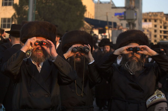 Ultra-Orthodox Jews of the Belz Hasidic Dynasty use binoculars to watch the wedding ceremony of Rabbi Shalom Rokach, the Grandson of the Belz Rabbi to Hana Batya Pener, in Jerusalem on May 21, 2013. Some 25,000 Ultra-Orthodox Jews participated in one of the biggest weddings in the past few years. (Photo by Menahem Kahana/AFP Photo)